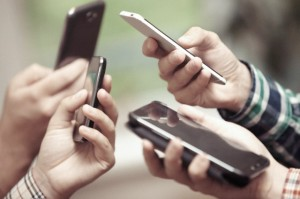 Close-up view of people's hands with cell phones