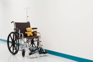 Wheelchair with teddy bear in hospital corridor